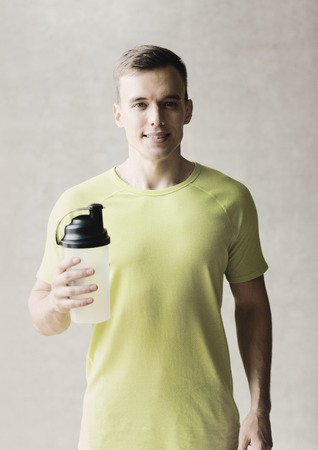 water bottles: sport, fitness, lifestyle and people concept - smiling man with protein shake bottle in gym