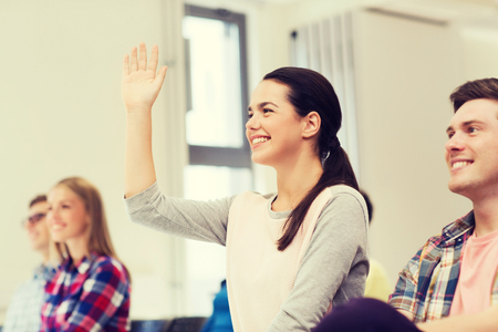 raising: education, high school, teamwork and people concept - group of smiling students raising hand in lecture hall
