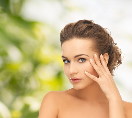 health and beauty concept - face and hands of beautiful woman with updo