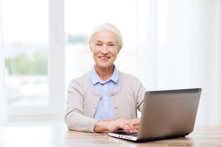 mujer alegre: technology, age and people concept - happy senior woman with laptop computer at home