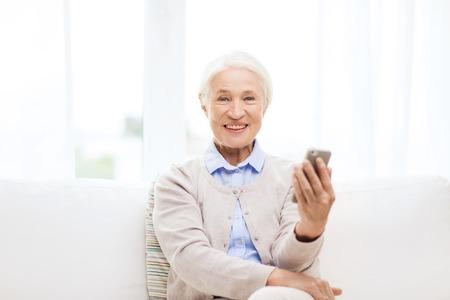 technologie, communicatie leeftijd en mensen concept - gelukkige senior vrouw met smartphone thuis