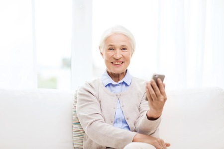 technology, communication age and people concept - happy senior woman with smartphone at home Standard-Bild