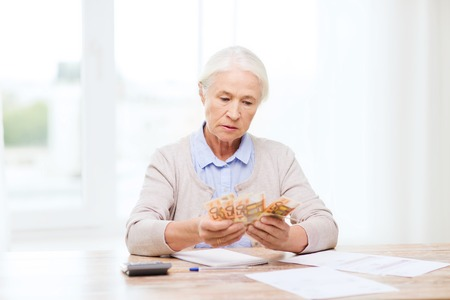 business savings: business, savings, annuity insurance, age and people concept - senior woman with calculator and bills counting euro money at home Stock Photo