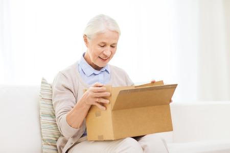 Alter, Lieferung, Mail, Versand und Menschen Konzept - glückliche lächelnde ältere Frau, die in offene Paket Box zu Hause