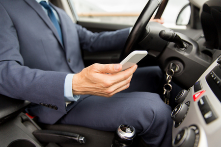 transport, business trip, technology and people concept - close up of young man with smartphone driving car