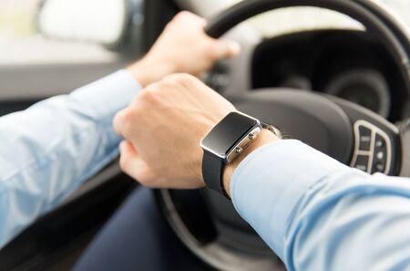 Verkehr, Geschäftsreise, Technologie, Zeit und Personen-Konzept - Nahaufnahme des Menschen mit der Armbanduhr Auto fahren