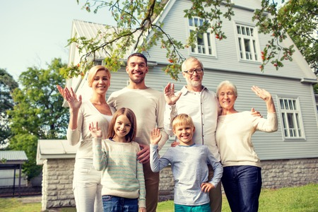 home front: family, generation, gesture, home and people concept - happy family standing in front of house waving hands outdoors Stock Photo