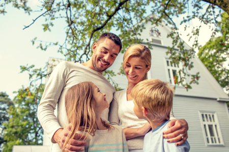 house family: family, happiness, generation, home and people concept - happy family standing in front of house outdoors Stock Photo