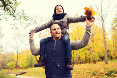 shoulder ride: family, childhood, season and people concept - happy father and son having fun in autumn park