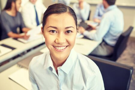businesspeople: business, people and teamwork concept - smiling businesswoman with group of businesspeople meeting in office