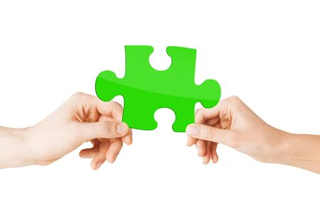 economize: nature, ecology, energy saving and people concept - close up of couple hands with green puzzle Stock Photo