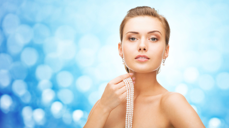 bride bangle: beauty, luxury, people, holidays and jewelry concept - beautiful woman with pearl earrings and bracelet over blue lights background Stock Photo