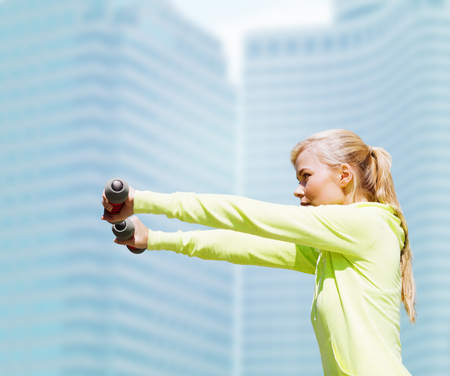 shaping: sport and lifestyle - young sporty woman with light dumbbells outdoors