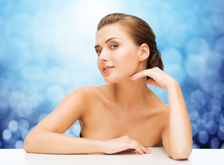 attractive  female: beauty, people and health concept - beautiful young woman touching her face over blue lights background