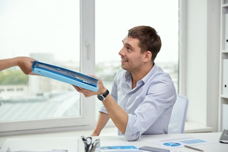hand paper: business, people and paperwork concept - happy businessman taking folder with papers from secretary in office
