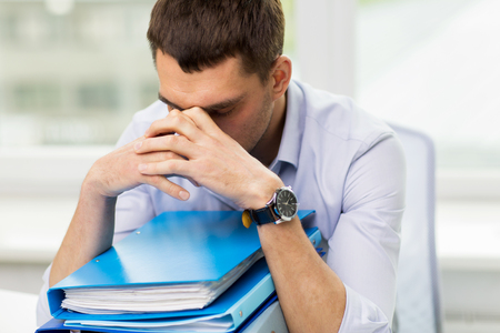 file clerks: business, people, deadline, stress and paperwork concept - sad businessman with stack of folders at office Stock Photo