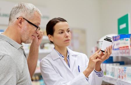 pharmaceutics: medicine, pharmaceutics, health care and people concept - pharmacist showing drug to senior man customer at drugstore