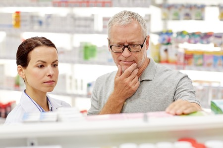finding a cure: medicine, pharmaceutics, health care and people concept - pharmacist showing drug to senior man customer at drugstore