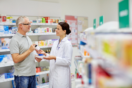 prescription medicine: medicine, pharmaceutics, health care and people concept - happy pharmacist giving drug to senior man customer and taking prescription at drugstore