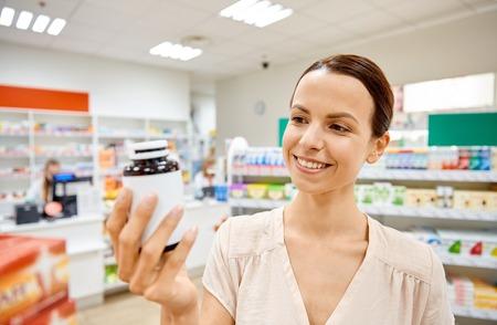 pharmaceutics: medicine, pharmaceutics, health care and people concept - happy female customer with drug jar at pharmacy