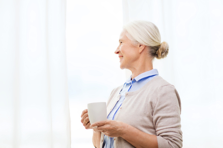 woman alone: age, drink and people concept - happy smiling senior woman with cup of tea or coffee at home