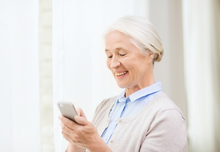 technology, communication age and people concept - happy senior woman with smartphone texting message at home Banco de Imagens