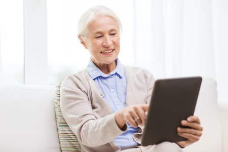 computer age: technology, age and people concept - happy senior woman with tablet pc computer at home Stock Photo