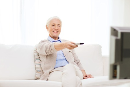 changing channel: technology, television, age and people concept - happy senior woman watching tv and changing channel with remote control at home