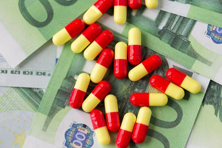 drug trafficking: medicine, finance, health care and drug trafficking - medical pills or drugs and euro cash money on table
