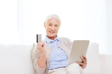emoney: technology, online shopping, age and people concept - happy senior woman with tablet pc computer and credit or bank card at home
