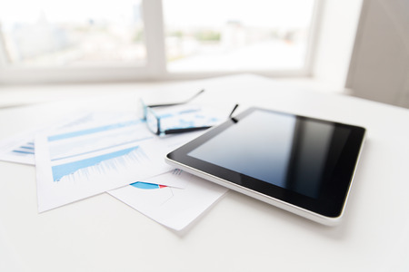 business, objects and technology concept - close up of tablet pc computer, eyeglasses and papers on office table