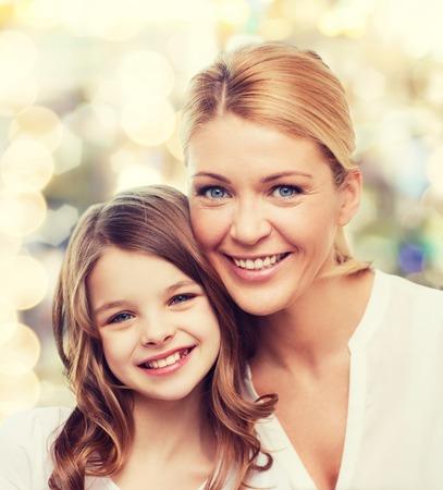 familie, jeugd, geluk en mensen - glimlachende moeder en meisje op de achtergrond verlichting