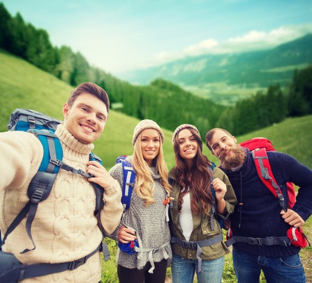 self discovery: adventure, travel, tourism, hike and people concept - group of smiling friends with backpacks making selfie over alpine hills background