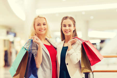 happy shopping: sale, consumerism and people concept - happy young women with shopping bags in mall Stock Photo