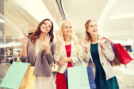 consumerism: sale, consumerism and people concept - happy young women with shopping bags waving hands in mall