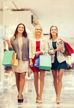 la venta, el consumo y el concepto de las personas - mujeres jóvenes felices con bolsas de compras caminando en mall