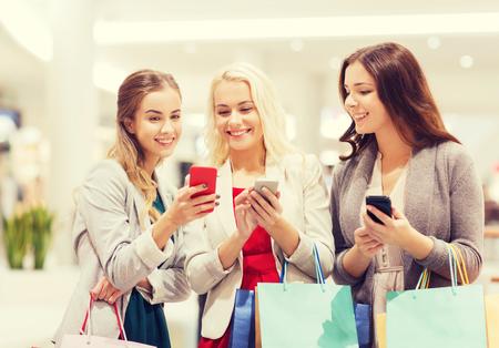 chicas de compras: la venta, el consumo, la tecnología y el concepto de las personas - mujeres jóvenes felices con teléfonos inteligentes y las bolsas de la compra en centro comercial