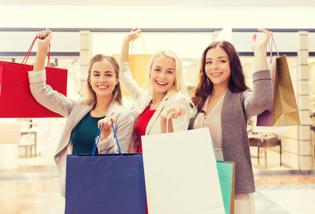 succesful: sale, consumerism and people concept - happy young women raising hands with shopping bags in mall