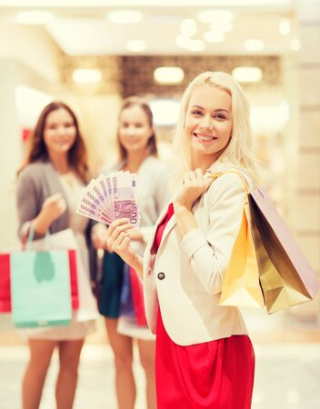 woman holding money: sale, consumerism and people concept - happy young women with shopping bags and euro cash money in mall