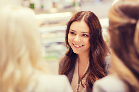 women friendship: communication, friendship and people concept - happy young women meeting and talking in mall or city