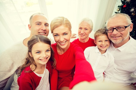 familiares, vacaciones, generación, Navidad y la gente concepto - sonriendo familia con cámara o un teléfono inteligente haciendo autofoto en casa