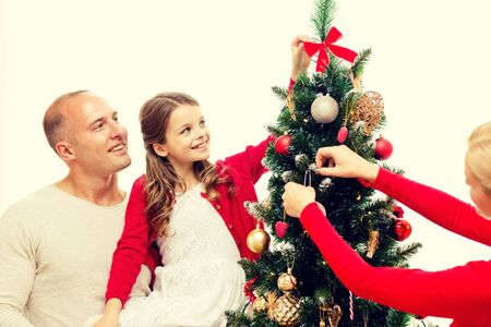 home decorating: family, holidays, generation and people concept - smiling family decorating christmas tree at home