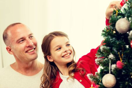 decorating: family, holidays, generation and people concept - smiling girl with father decorating christmas tree at home