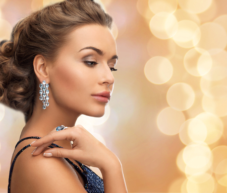 brilliants: people, holidays and glamour concept - beautiful woman in evening dress wearing ring and earrings over beige lights background Stock Photo