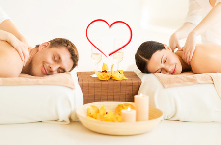 Beleza: spa, beleza, amor e conceito da felicidade - casal sorrindo com velas, flores e taças de champanhe que começ a massagem no salão de beleza spa