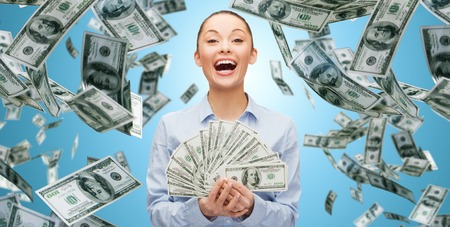 business, money, finance, people and banking concept - happy laughing businesswoman with heap of dollar cash money over blue background