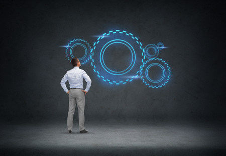 business, people, technology and concept - businessman looking at cogwheel projection over concrete room background from back Imagens