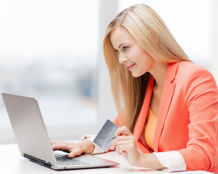 businesswoman card: smiling businesswoman with laptop and credit card
