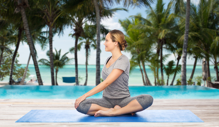 beach mat: fitness, sport, people and healthy lifestyle concept - woman making yoga in twist pose on mat over hotel resort pool on tropical beach background