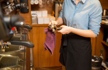 equipment, coffee shop, people and technology concept - close up of woman cleaning espresso machine holder at restaurant bar Stock Photo